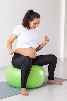 La donna incinta allegra balla mentre è seduta sulla palla fitness. benessere gravidanza, stile di vita sano e concetto positivo.