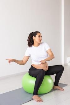 La donna incinta allegra balla mentre è seduta sulla palla fitness benessere gravidanza stile di vita sano