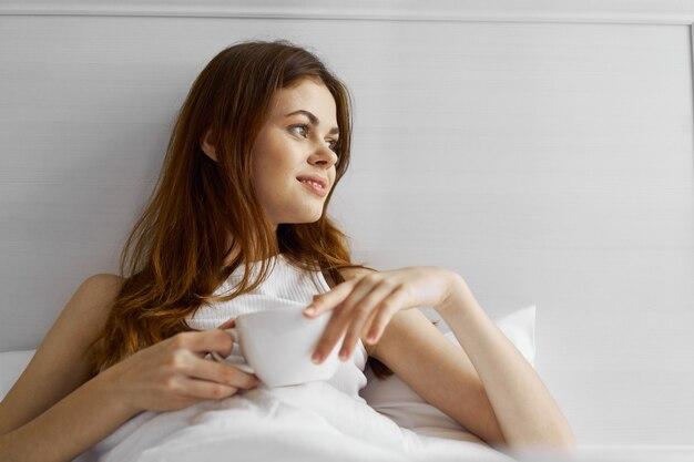 La donna graziosa allegra si trova a letto in camera da letto