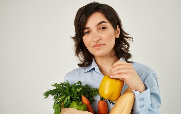 Allegra bella donna in una camicia con un pacchetto di prodotti per la casa di cibo sano consegna