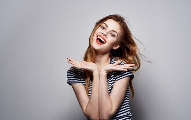 Fondo isolato emozioni di cosmetici di sorriso di fascino della maglietta a strisce della donna graziosa allegra. foto di alta qualità Foto Premium