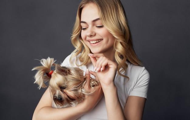 Una bella donna allegra con una maglietta bianca tiene in mano un cane di piccola taglia.