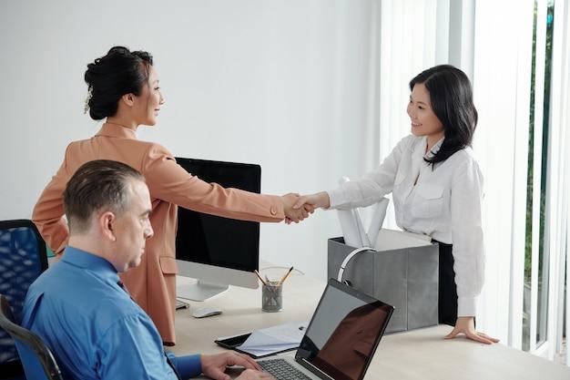 Donna d'affari piuttosto giovane allegra che stringe la mano ai colleghi nel suo nuovo posto di lavoro