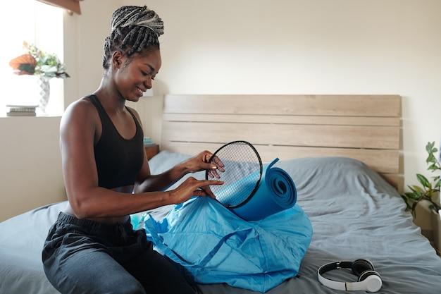 Una bella giovane donna allegra che imballa la borsa da palestra, sta mettendo dentro un tappetino da yoga e una racchetta da badminton
