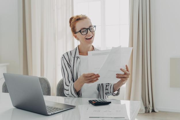 Il contabile professionista allegro prepara la relazione finanziaria annuale esamina i documenti