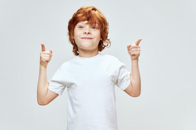 Allegro ragazzo dai capelli rossi gesticolare con le sue mani dita indice sorriso t-shirt bianca copy space spazio grigio.