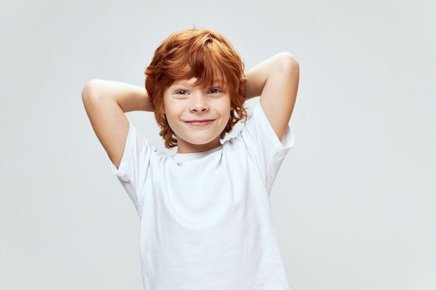 Allegro ragazzo dai capelli rossi che tengono le mani dietro la sua testa sorriso t-shirt bianca grigio muro isolato