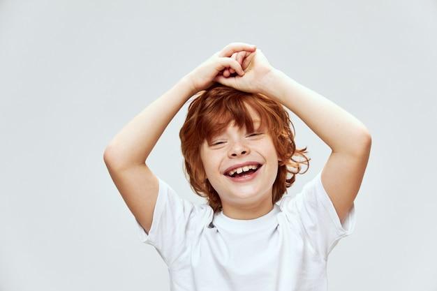 Allegro ragazzo dai capelli rossi sorriso emozioni mani sopra la testa