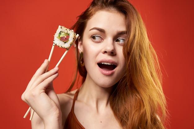 Primo piano allegro di divertimento di dieta dei rotoli di sushi della donna dai capelli rossi