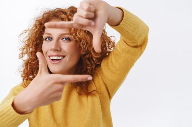 Allegra donna riccia rossa che immagina tiene la macchina fotografica, fa le mani della cornice e sorride guardando attraverso, cerca la prospettiva o l'angolo retto per scattare foto fantastiche, fotografare, muro bianco