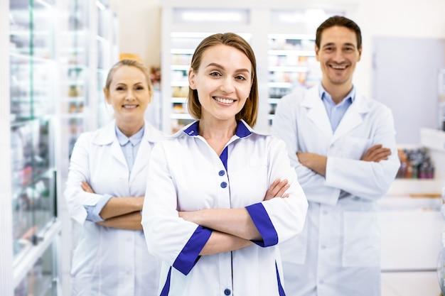 Allegri affidabili tre farmacisti in piedi a braccia incrociate, pronti a consigliare e fornire servizi