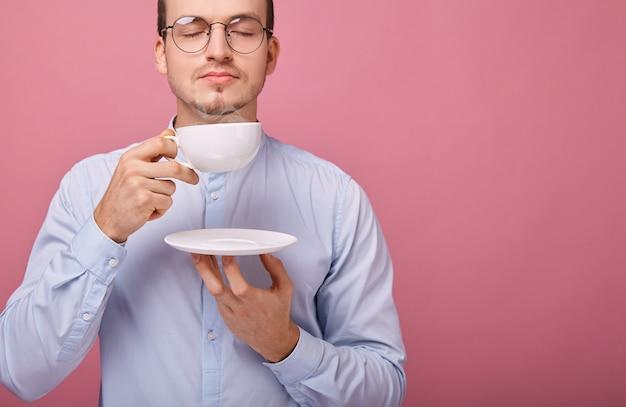 Un allegro studente reattivo in bicchieri con bordo nero sta riposando con una tazza di caffè bianca