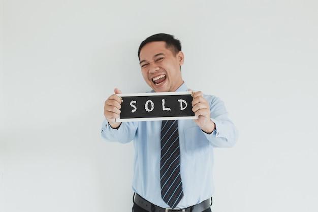 Venditore allegro che indossa camicia e cravatta blu che mostra il cartello venduto su sfondo bianco