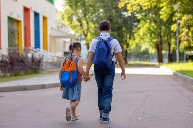 Allegri scolari, una bambina e un ragazzo in camicia bianca con zaini