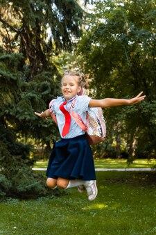 Studentessa allegra con uno zaino rosa sta saltando sullo sfondo della natura.