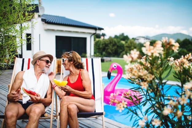 Allegra coppia senior seduta a bordo piscina all'aperto nel cortile, parlando.