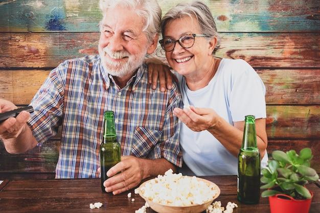 Coppia senior allegra che guarda una partita di calcio in tv, beve birra e mangia popcorn. sfondo in legno