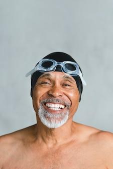 Uomo anziano allegro che indossa occhiali da nuoto