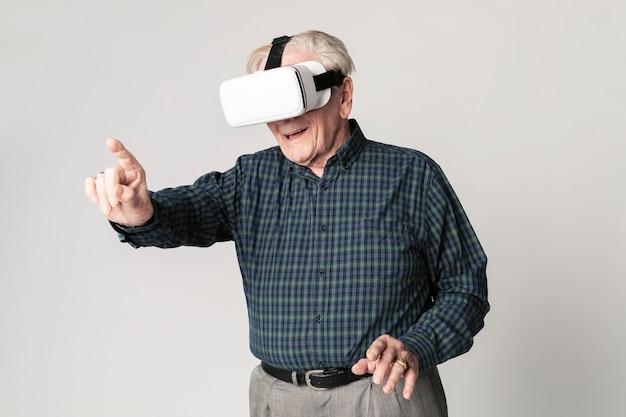 Uomo anziano allegro che indossa occhiali per realtà virtuale