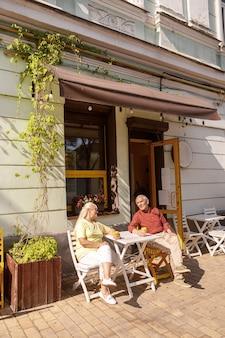 L'uomo e la donna senior allegri con le tazze di caffè si siedono in caffè della via
