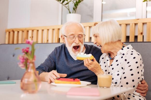 Donna senior allegra che tiene eclair e uomo anziano che lo mangia