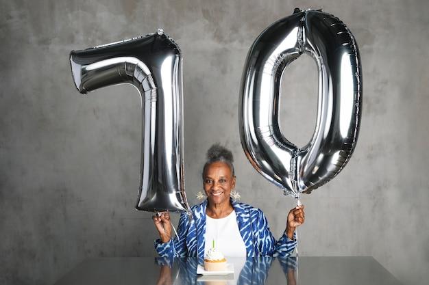 Allegra donna anziana che tiene in mano palloncini d'argento per la sua celebrazione del settantesimo compleanno
