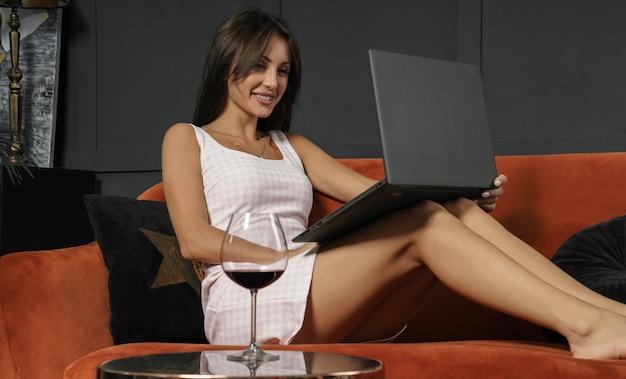 Donna sexy allegra utilizzando laptop e bere vino a casa sul divano
