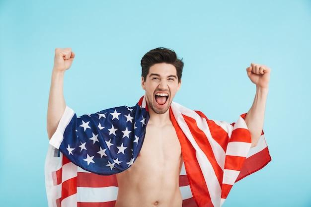 Allegro uomo a torso nudo in piedi isolato, con indosso la bandiera americana, celebrando il successo
