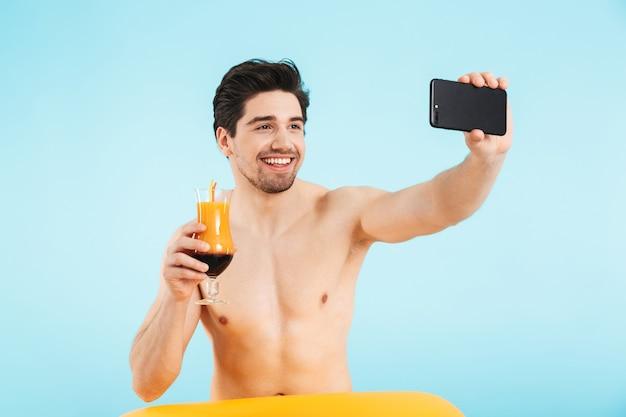 Uomo allegro senza camicia che indossa un anello gonfiabile che si fa un selfie mentre beve un cocktail