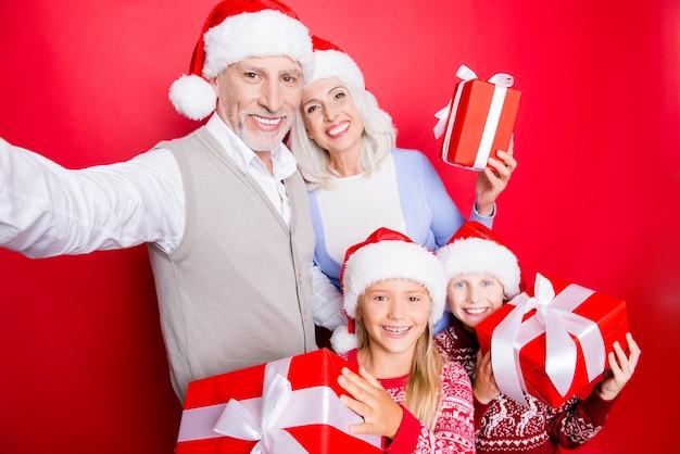Fratelli allegri e coppia senior sposata prendono e mostrano doni con nastri, in abbigliamento carino x mas lavorato a maglia, isolato sullo spazio rosso, il nonno è fotografo, la nonna fa ricordi