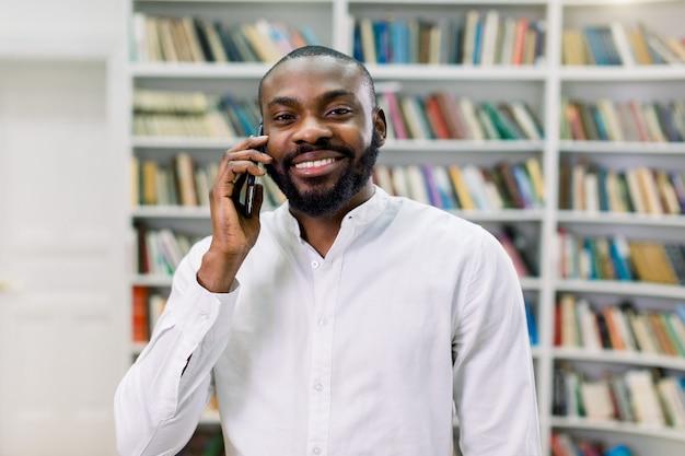 Studente maschio o uomo d'affari africano sorridente allegro, indossando camicia bianca, parlando al telefono, stando nella biblioteca moderna