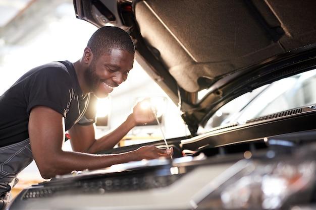 L'uomo afro sorridente allegro si diverte a riparare il cofano dell'auto