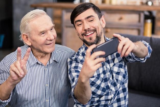Uomo invecchiato sorridente allegro che posa davanti alla macchina fotografica mentre fa i selfie con suo figlio