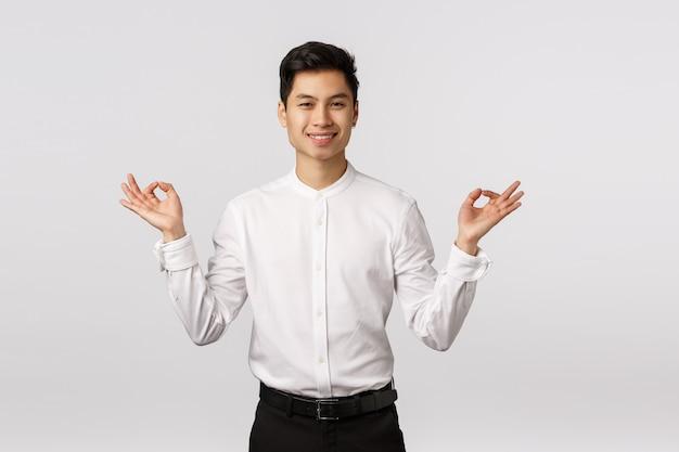 Giovane imprenditore asiatico sorridente allegro con la camicia bianca sollevata