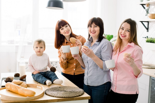 Giovani donne attraenti sorridenti allegre, donna invecchiata centrale e piccola neonata sveglia che mangiano i biscotti e i bigné e che bevono la cucina del caffè a casa. concetto di happy mothers day, cucinare insieme