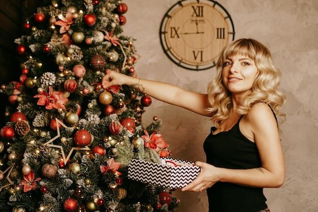Allegra donna bionda sorridente decora l'albero di natale con le palle tempo di natale felice vacanza albero di natale capodanno sorpresa presente