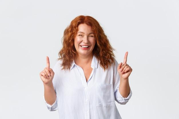 Allegra sorridente e spensierata, bella donna di mezza età con i capelli rossi, punta il dito verso l'alto mentre ride e sorride ottimista, mostrando prezzi esilaranti, offerte speciali, muro bianco.