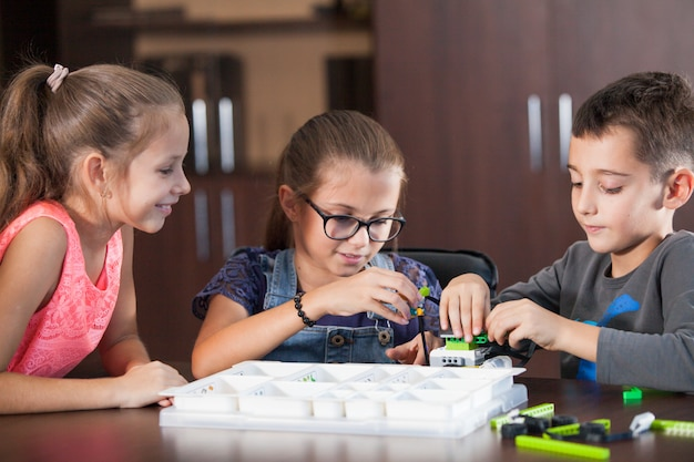 I bambini sorridenti allegri stanno costruendo un costruttore.