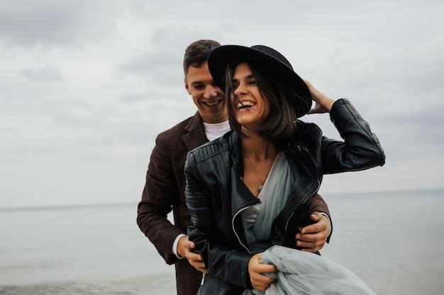 Coppie sorridenti allegre nell'amore che abbraccia in riva al mare.