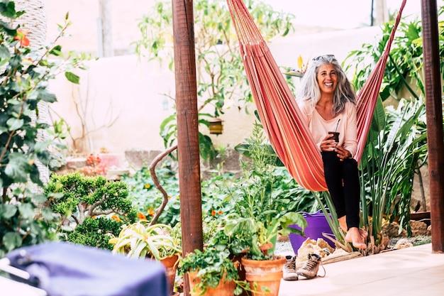 Allegro sorridente diversità persone concetto con bella donna adulta alla moda con i capelli lunghi bianchi che ride sedersi su un'amaca a casa in giardino bevendo un tè