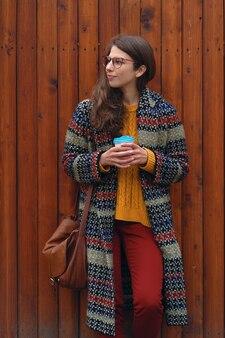 Ragazza sorridente allegra che tiene il caffè per andare all'aperto sulla parete di legno. giovane donna che gode del tempo e che sorride.