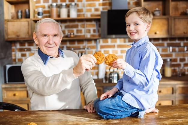 Ragazzino sorridente allegro che si siede sulla tavola mentre mangia i biscotti fatti in casa