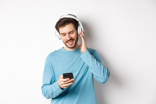 Allegro uomo sorridente ascoltando musica e guardando smartphone, leggendo il messaggio sul telefono, in piedi su sfondo bianco.