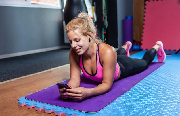 Donna sportiva sorridente allegra che riposa dopo l'esercizio sdraiata sul tappetino e utilizza lo smartphone