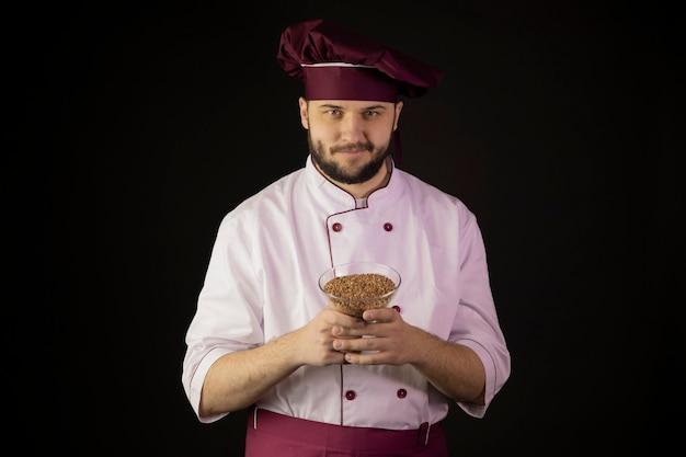 Allegro sorridente giovane chef barbuto in uniforme tenendo la ciotola di cereali