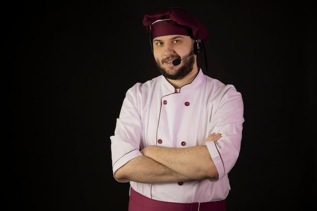 Allegro sorridente giovane chef maschio barbuto in uniforme che indossa la cuffia avricolare parlando nel microfono
