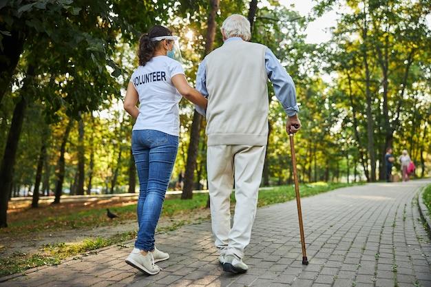 Assistente sociale allegro in camicia bianca che cammina con un uomo anziano per strada