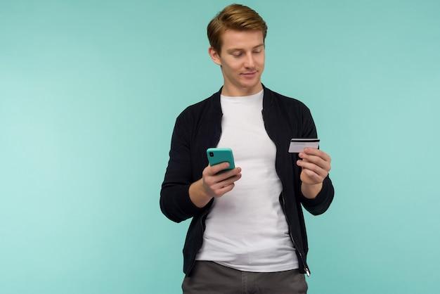 Il ragazzo dai capelli rossi sportivo allegro effettua il pagamento online e guarda lo schermo dello smartphone su uno spazio blu.
