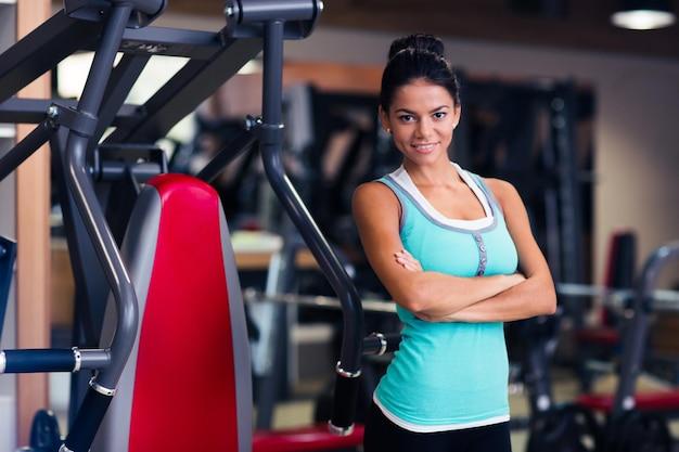 Allegro sport donna in piedi con le braccia incrociate in palestra