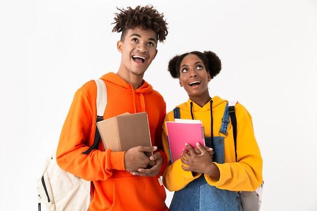 Studenti allegri che indossano zaini in possesso di quaderni, isolati su muro bianco